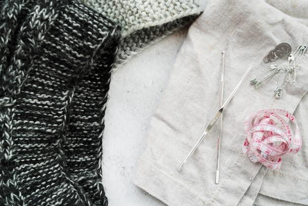Agulhas de crochê; malha de malha; fita métrica; alfinetes de segurança em pano de fundo texturizado branco Foto gratuita