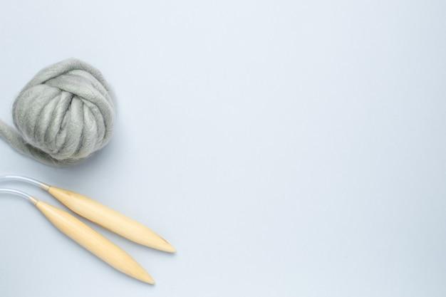 Agulhas de tricô circulares e grosso fio cinza sobre fundo azul Foto Premium