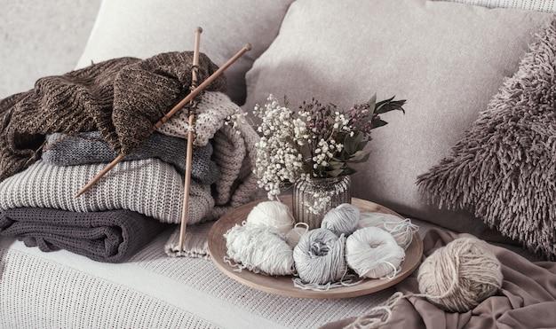 Agulhas de tricô de madeira vintage e linhas em um sofá aconchegante com almofadas e um vaso de flores Foto Premium