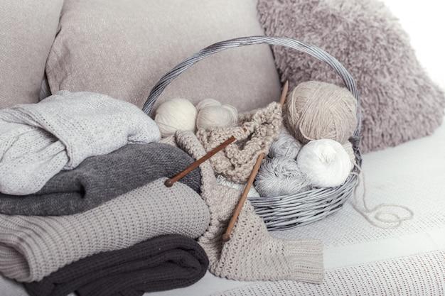 Agulhas de tricô de madeira vintage e linhas em uma grande cesta em um sofá aconchegante com blusas. ainda vida foto Foto gratuita