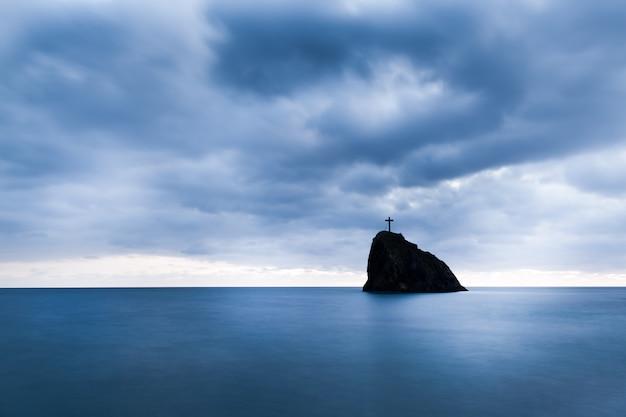 Ainda águas do mar, pedras duras e cruzam no pico da rocha na noite num dia de verão com céu sombrio no fundo Foto Premium