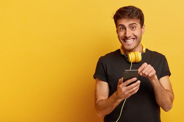Ainda bem que o homem europeu aponta para a tela do smartphone, usa fones de ouvido amarelos e camiseta preta casual Foto gratuita