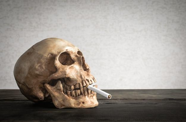 Ainda o crânio da vida de um esqueleto com cigarro ardente, para de fumar o conceito da campanha com espaço da cópia. Foto Premium