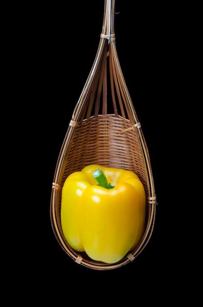 Ainda vida com pimento são colocados em uma cesta de madeira, isolada no preto Foto Premium