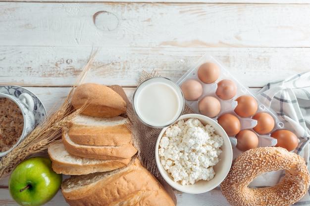 Ainda vida com produtos lácteos, leite, ovos, pão Foto Premium