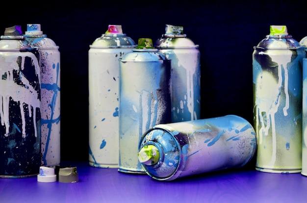 Ainda vida com um grande número de latas de pulverizador coloridas usadas do aerossol Foto Premium