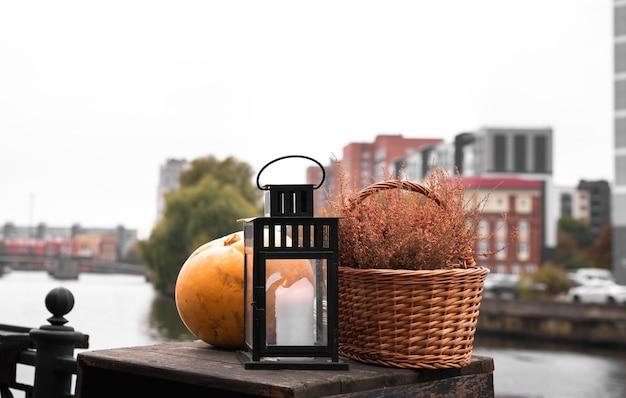 Ainda vida de abóbora, lâmpada, cesta de vime, aterro da cidade, decoração, rua, halloween. Foto Premium