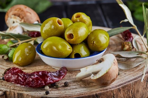 Ainda vida de azeitonas verdes frescas, pimenta vermelha e cogumelos frescos com folhas de oliveira em um close de madeira escura Foto Premium