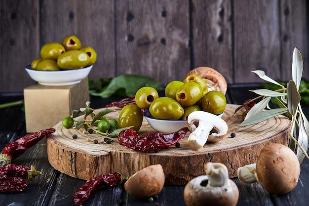 Ainda vida de azeitonas verdes frescas, pimenta vermelha e cogumelos frescos com folhas de oliveira em um escuro de madeira Foto Premium