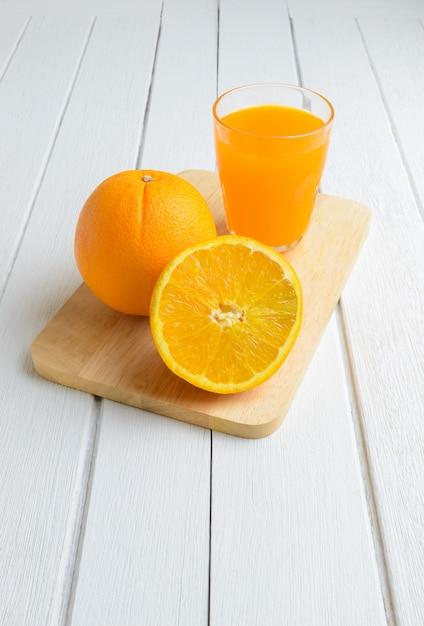 Ainda vida fruta laranja fresca, suco de laranja na mesa de madeira branca vintage Foto Premium