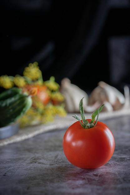 Ainda vida rústica com legumes frescos: tomates vermelhos, pepinos verdes, alho, aneto em um fundo escuro. Foto Premium