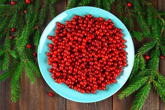 Airela, foxberry, cranberry, lingonberry em um prato de cerã ¢ mica azul em uma mesa de madeira marrom. Foto Premium