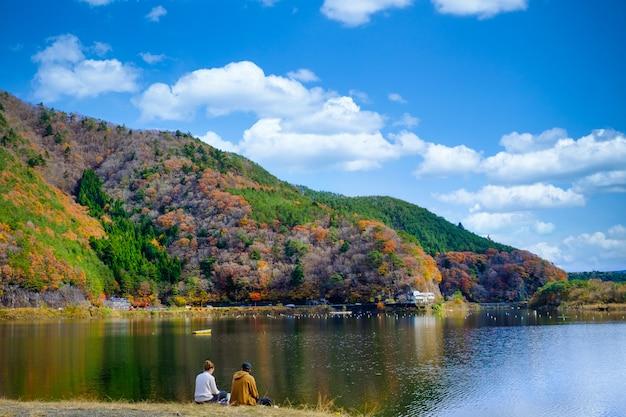 Ajardine a vista folhas de outono do lago kawaguchiko e casal sentado junto ao rio no japão Foto Premium