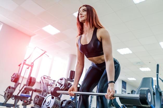 Ajuste a barra de levantamento da jovem mulher que olha focalizada, malhando em uma academia. mulher jovem e bonita exercícios com barra. Foto Premium