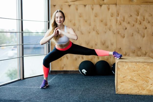 Ajuste a caixa de jovem pulando em um ginásio de estilo crossfit. atleta feminina está realizando saltos de caixa no ginásio. Foto gratuita