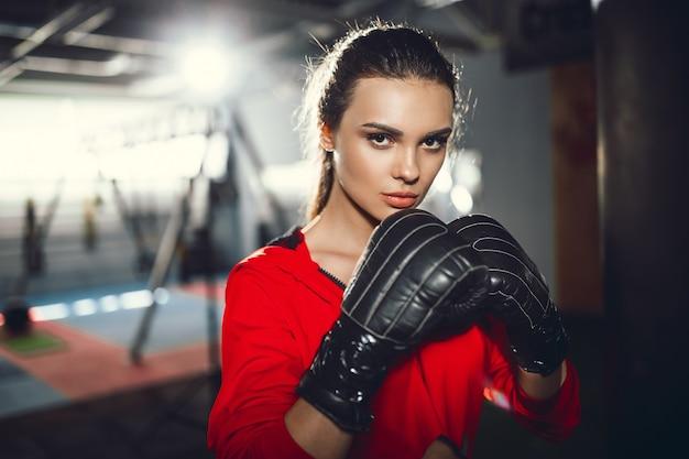Ajuste a mulher morena bonita magro jovem boxe no sportswear. luz fraca e escura. Foto Premium