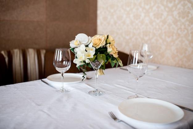 Ajuste da mesa de jantar decorado com flores. Foto Premium