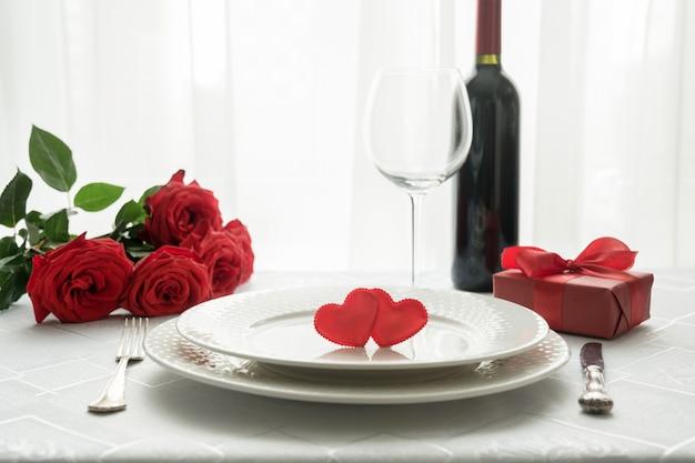 Ajuste de lugar da tabela do dia de valentim com rosas vermelhas, caixa de presente, e vinho. convite para uma data. Foto Premium