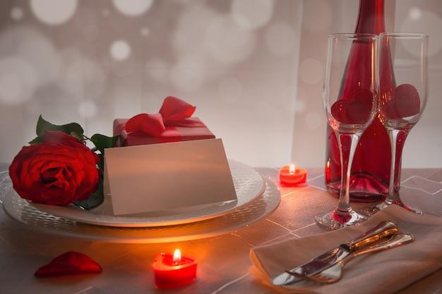 Ajuste de lugar da tabela do dia de valentim com rosas vermelhas e champanhe. convite para uma data. Foto Premium