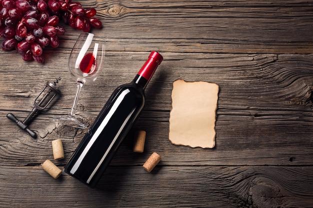 Ajuste do jantar do feriado com vinho tinto e presente na madeira rústica. vista superior com espaço para suas saudações. Foto Premium