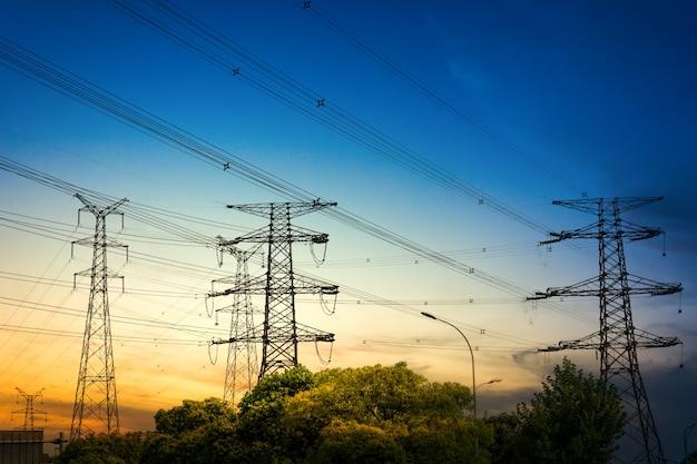 Ajuste do sol atrás da silhueta das torres de eletricidade Foto gratuita