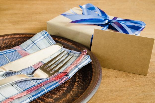 Ajuste festivo da tabela com cartão e presente. Foto Premium
