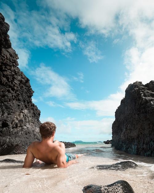 Ajuste masculino deitado e relaxando na praia perto de grandes rochas negras e olhando para o mar Foto gratuita