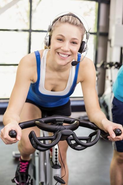 Ajuste o grupo de pessoas que usam bicicleta ergométrica juntos em crossfit Foto Premium