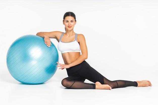 Ajuste o instrutor de pilates jovem morena mostrando exercícios diferentes com equipamentos básicos de pilates, incluindo uma bola. fundo branco Foto Premium