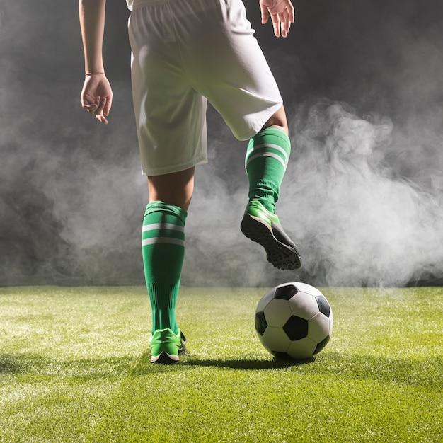 Ajuste o jogador de futebol no sportswear com bola Foto gratuita