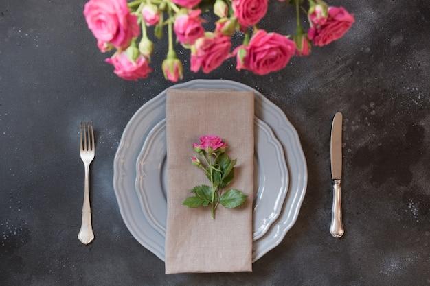 Ajuste romântico da tabela com as rosas cor-de-rosa como a decoração, o dishware do vintage, a pratas, e as decorações. Foto Premium