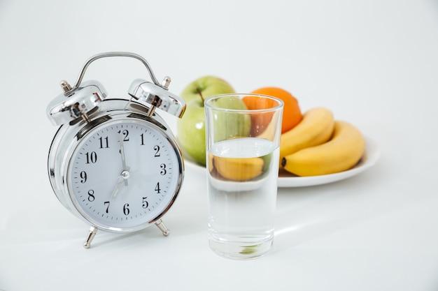 Alarme e copo de água perto de frutas Foto gratuita
