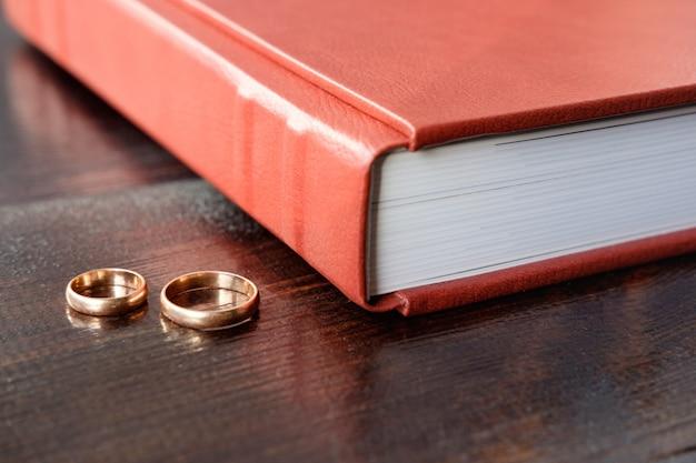 Álbum de casamento marrom com dois anéis de casamento deite na mesa de madeira marrom Foto Premium