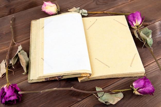 Álbum de fotos vintage na madeira com flores secas. Foto Premium
