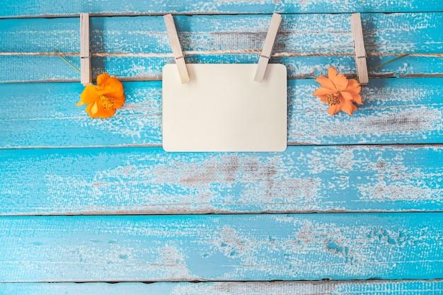 Álbum de quadro de fotos em branco e flores penduradas no fundo de madeira azul vintage Foto Premium
