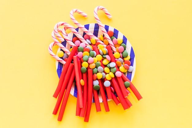 Alcaçuz, pedras preciosas e doces de bengala de natal na placa sobre o pano de fundo amarelo Foto gratuita