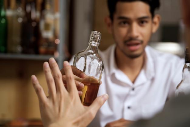 Álcool de recusa de mão do homem sentado do lado oposto. Foto Premium