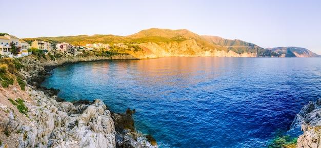 Aldeia de assos em um penhasco ao pôr do sol noturno em kefalonia, grécia Foto Premium