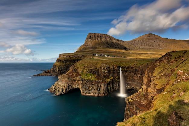 Aldeia de gasadalur e sua icônica cachoeira de vagar nas ilhas faroe Foto Premium