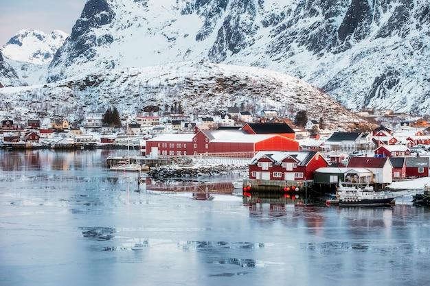 Aldeia de pescadores de reine na costa gelada com montanha de neve Foto Premium
