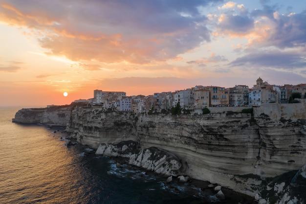Aldeia em um penhasco sobre o oceano ao pôr do sol Foto gratuita