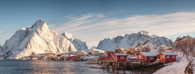 Aldeia escandinava com montanha de neve no litoral na manhã Foto Premium