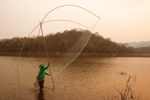 Aldeões estão pegando peixe por armadilha de peixe (armadilha líquida) no reservatório Foto Premium