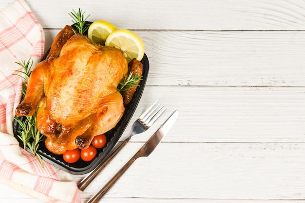 Alecrim de frango inteiro assado e pimenta malagueta - assado frango grelhado churrasco comida deliciosa na mesa de jantar no feriado comemorar, vista superior Foto Premium