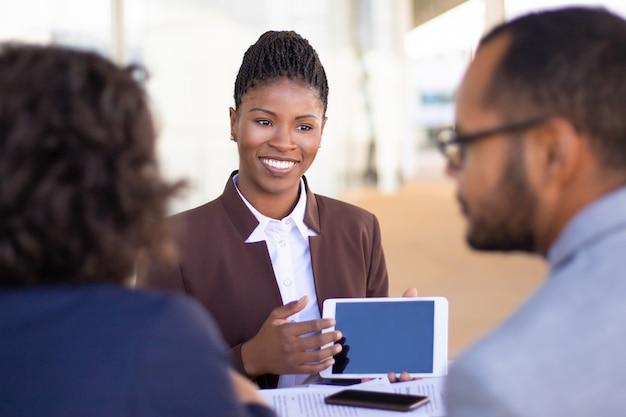 Alegre agente de vendas bem-sucedido, apresentando conteúdo no tablet Foto gratuita