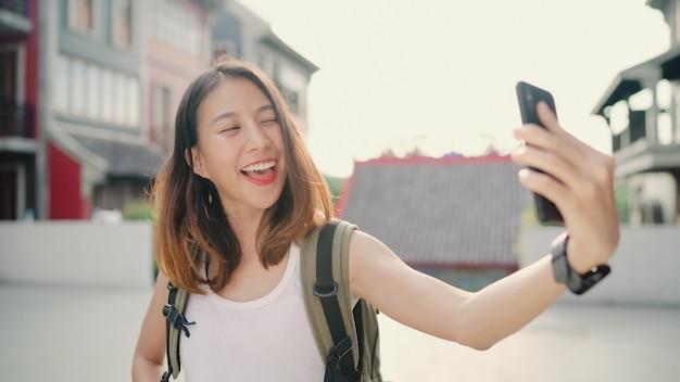 Alegre bonita jovem mochileiro asiáticos blogueiro mulher usando smartphone tomando selfie Foto gratuita