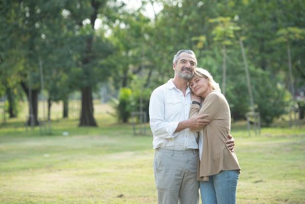 Alegre casal sênior ativo com bicicleta caminhando juntos pelo parque. atividades perfeitas para idosos no estilo de vida da aposentadoria. Foto Premium