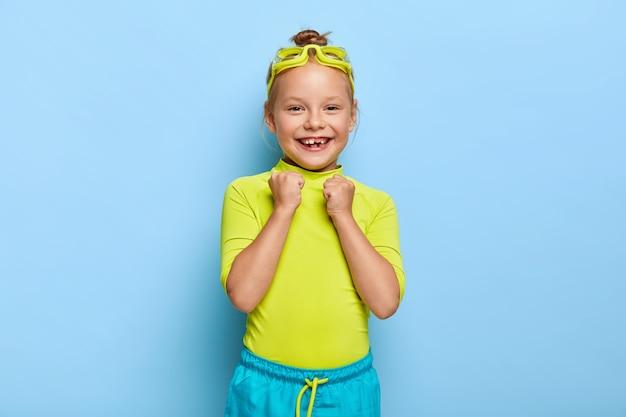 Alegre criança pequena do sexo feminino levanta os punhos cerrados, regozija-se com a natação bem-sucedida, usa óculos de proteção, roupas brilhantes, tem um sorriso cheio de dentes, desfruta de seu hobby favorito durante as férias de verão. infância feliz Foto gratuita