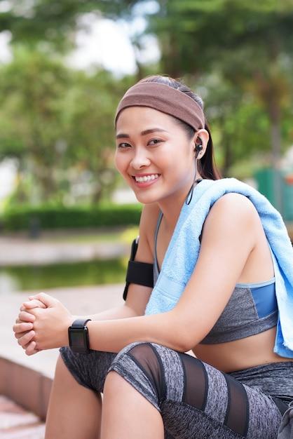 Alegre desportista asiática sentado no parque Foto gratuita