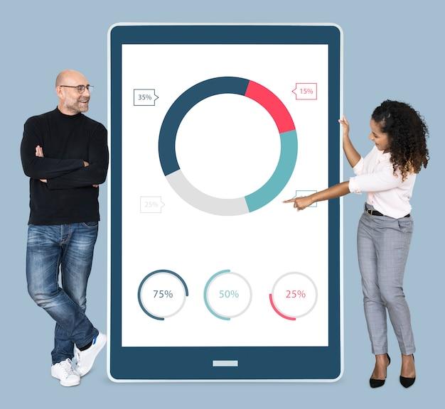 Alegre diversas pessoas mostrando o gráfico de pizza em um tablet Foto gratuita